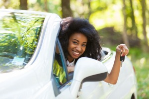Young beautiful black teenage driver holding car keys driving her new car