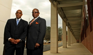 100325 Atlanta, Ga., -- The Russell Brothers of H.J. Russell & Company, CEO Michael Russell, left, and President H. Jerome (glasses) pose for a photograph in front of one of their most recent projects JC Young Middle School Thursday morning in Atlanta, Ga., March 25, 2010. H.J. Russell Company is still working on the grounds of the school but the building is complete with students and staff moving into the building last January 2010. The H.J. Russell Company, like many other construction companies, is in survival mode. The brothers work hard everyday to make sure the company lives to fight another day. Jason Getz, jgetz@ajc.com